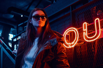Young stylish girl wearing a hoodie coat and sunglasses standing on stairs at underground nightclub with industrial interior Wall mural