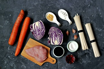 Ingredients for cooking noodles stir frying with vegetables and turkey: turkey fillet, carrots, red cabbage, wheat noodles, soy sauce, garlic, cornstarch, dried ginger, sugar, wine vinegar. Top view.