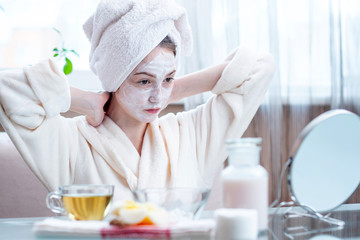Beautiful happy woman with cosmetic natural mask on her face looking at her skin. Skin care and Spa treatments at home