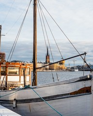 Old sailing boat in port with the sity on the background at the sunset