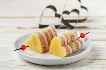 Mini sandwiches parmesan cheese ham bread on skewers in the form of hearts. Valentine's day. Breakfast for loved ones. Selective focus and copy space