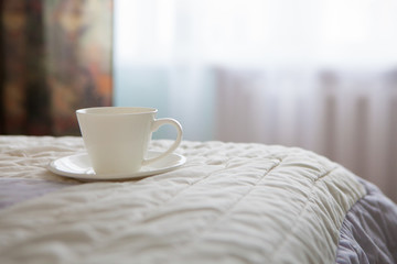 Morning cup of coffee on the background of the bed and the window