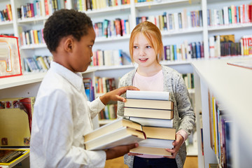 Zwei Schüler in der Bücherei tragen Bücher