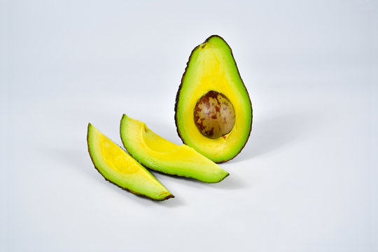 Fresh avocado cut in half with seed  isolated on white background.