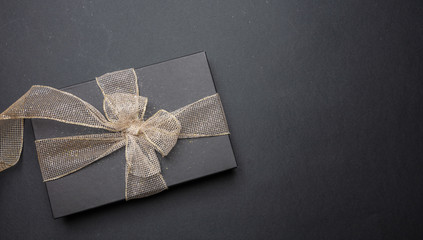 Wall Mural - Black gift box with shiny ribbon on black background, top view