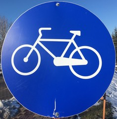 old round bicycle lane sign on the road