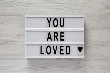 Lightbox with text 'You are loved' on a white wooden surface, top view. Flat lay, overhead. Close-up.