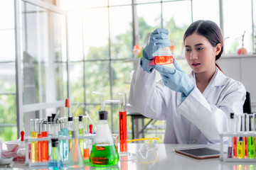 Attractive scientist looking chemical sample in flask at laboratory with lab glassware background. Science or chemistry research and development concept.