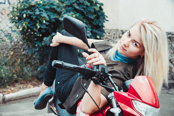 Biker woman sitting on v motorcycle. Outdoor lifestyle toned portrait
