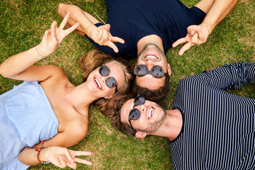 Peace sign pals lying on grass in sunglasses, portrait