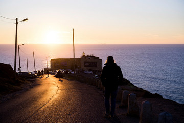the man at sunset goes to the lighthouse, Portugal, Nazaré.