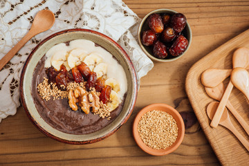 Cocoa Acia bowl with slices banana, fresh dates, candied walnuts and bee pollen topping on a brown wooden background with embroided napkins and wooden spoons