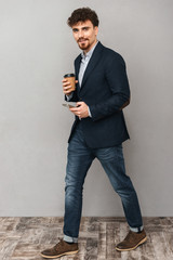 Handsome young business man isolated over grey wall background using mobile phone drinking coffee.