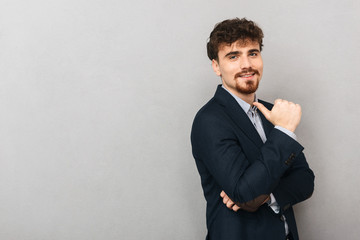 Business man isolated over grey wall background pointing.