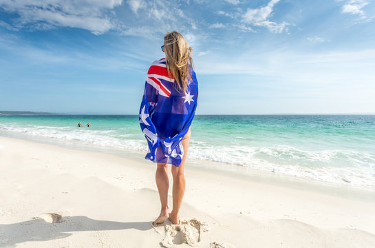 Woman standing on beach with flag wrapped around her