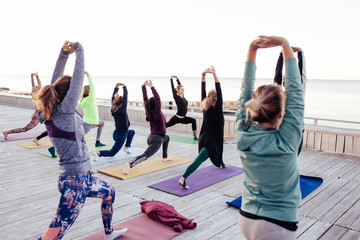 Group of sporty people doing stretching exercise as trainer helps in yoga lesson at wooden fitness terrace on the beach. Teacher assists to make warrior pose, Yoga Practice Exercise Class Concept