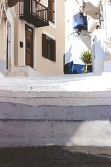 Stairs in the narrow street of Neorio town on Poros island, Greece; summer background
