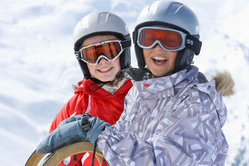 Children with goggles on winter vacation holding sled smiling at camera