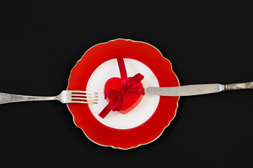 Red heart with a ribbon on a red plate.