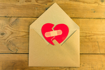 Red broken heart in an envelope.