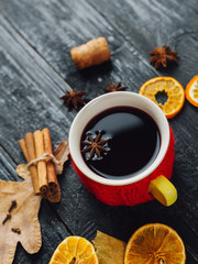 Mulled wine with spice and orange on wooden background with autumn leaves