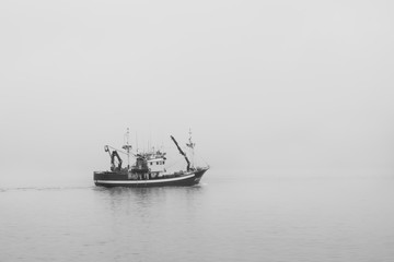 Fishing boat in the sea under the clouds and fog. Black and white