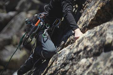 In de dag Alpinisme Climber climbs up the cliffs closeup. Climbing gear and equipment.