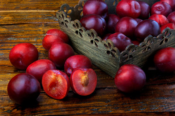 raw and fresh organic plums inside rustic fabric wooden box on rustic table