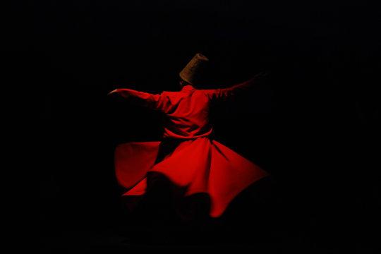 Whirling dervish in red garment on black background