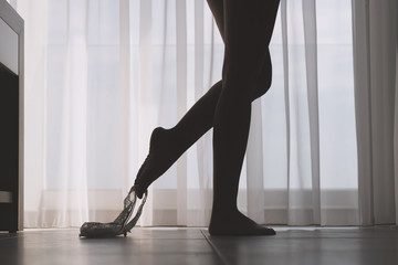 Bottom view of silhouette of beautiful woman with sexy legs taking off her white panties in a room against the backdrop of curtains