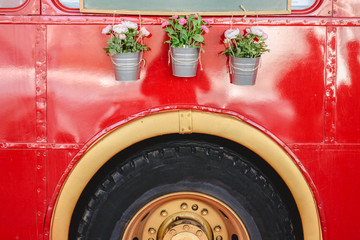 Pots with decoration plants hanging from a red bus in a vintage car exhibition.