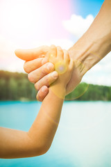 hands of a parent and child in nature in a park by the sea