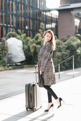 Schöne junge Frau freudig lachend mit Koffer auf dem Weg zum Urlaub Business Trip lifestyle