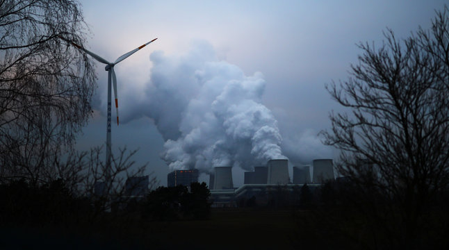 Water vapour rises from the cooling towers of the Jaenschwalde lignite-fired power plant of Lausitz Energie Bergbau AG (LEAG) beside a wind turbine in Jaenschwalde