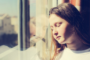 attractive sad teenage girl looking out of the window