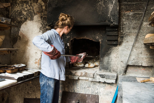Young woman baking loaves of bread in brick oven