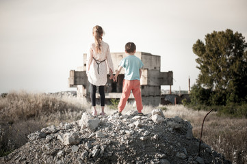 two poor refugees children standing with hope together holding hands on ruins of destroyed during war fighting home house