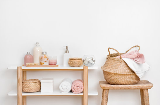 Spa bathroom interior with wooden shelf, stool and skincare products