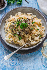 Pasta tagliatelle and mushrooms in creamy sauce with brandy and peppercorns
