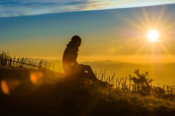 silhouette of lonely female traveler with  beautiful sunrise and mountains with blue sky  in the morning, chiang mai in thailand