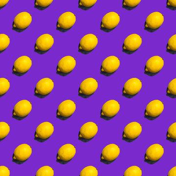Seamless pattern of lemons on violet background; flat lay