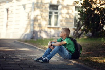 Sad alone boy sitting on road in the park outdoors.
