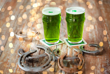 st patricks day, holidays and celebration concept - close up of glasses of green draft beer with shamrock and horseshoe
