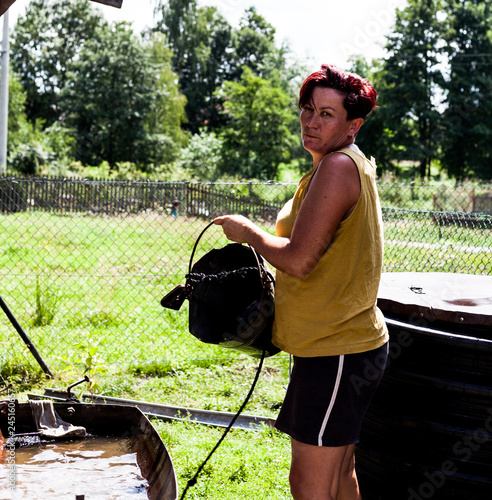 Middle aged woman filling the metal basin with natural water