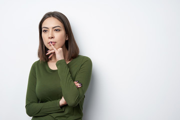 Thinking brunette woman standing by wall