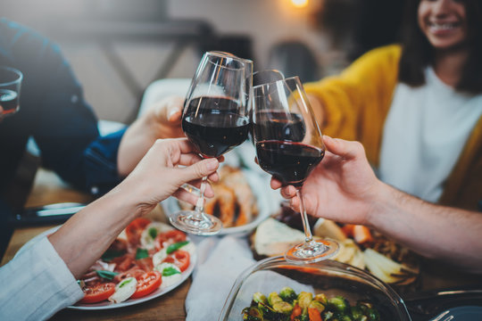 Say Cheers! Group of young people cheering with wine glasses during celebrate birthday in restaurant, Friendship Dinner Holidays Concept, best friends enjoying dinner at home