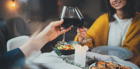 Romantic dinner concept, cropped image of happy couple enjoying healthy food and red wine during romantic dinner by candlelight, Celebration Love Relationship Date Concept