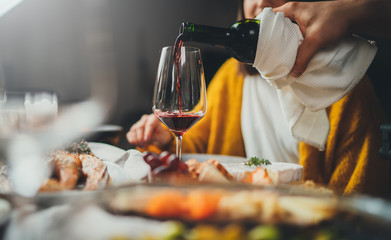 Romantic young caucasian man pouring red wine for his girlfriend during dinner date at restaurant enjoying healthy food, romantic atmosphere, happy couple celebrating concept