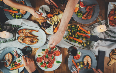 Top view shot of group of people enjoying healthy food and toasting at home, togetherness and friendship concept, filtered image, family dinner at home