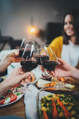 Vertical image of happy friends cheering with wine glasses at home, family celebrate anniversary enjoying healthy homemade food, Dinner Enjoyment Holidays Friendship Concept